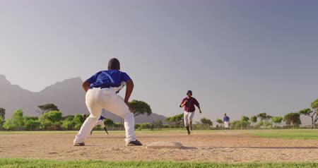 beisebol : Front view of a Caucasian male baseball player, running to a base during a baseball match on a sunny day, while an African American male catcher is catching the ball, in slow motion Stock Footage
