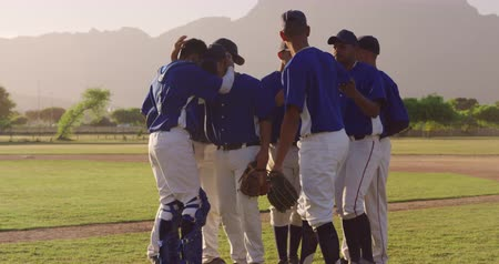 guantone : Side view of a multi-ethnic group of male baseball players, in a huddle on the field after a baseball game, embracing and celebrating on a sunny day, in slow motion