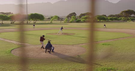 vleermuis : High angle view of baseball players in action on a baseball field during a game, seen through a net, on a sunny day, in slow motion