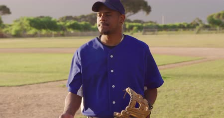guantone : Portrait of a mixed race male baseball player, standing on a baseball field on a sunny day, wearing a mitt, playing with a ball and smiling, in slow motion