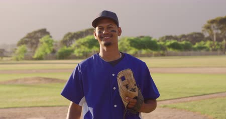 guantone : Portrait of a mixed race male baseball player wearing eye black and a baseball cap, standing on a baseball field on a sunny day, holding his mitt and looking to camera smiling, in slow motion