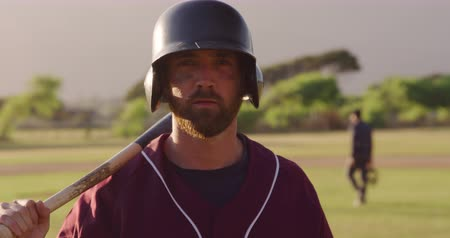 vleermuis : Portrait of a Caucasian male baseball player, a hitter, wearing helmet at a sports field on a sunny day, holding a baseball bat and resting it on his shoulder, looking straight to camera, in slow motion