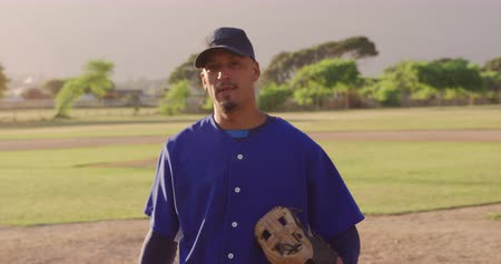 guantone : Portrait of a mixed race male baseball player wearing a baseball cap and a mitt, standing on a baseball field on a sunny day, looking to camera, in slow motion Filmati Stock