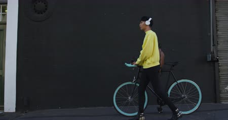 non binary : Side view of a fashionable mixed race transgender adult hanging out on a summer day in the city, wearing headphones, walking and wheeling his bicycle during a sunny day in slow motion.