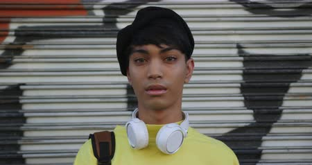non binary : Portrait of a fashionable mixed race transgender adult hanging out on a summer day in the city, standing in the street, smiling and looking straight into a camera in slow motion. Stock Footage