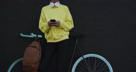 non binary : Front view of a fashionable mixed race transgender adult hanging out on a summer day in the city, standing in the street with his bicycle, using his smartphone in slow motion. Stock Footage
