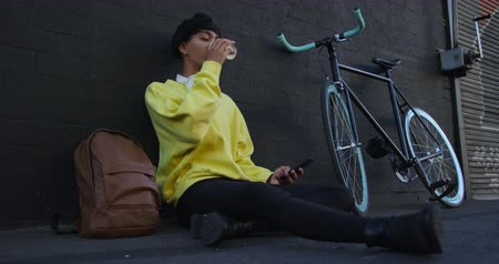 non binary : Side view of fashionable mixed race transgender adult hanging out on a summer day in the city, sitting in the street, drinking coffee and using his smartphone while his bicycle is leaning against the wall in slow motion.