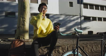 non binary : Front view of fashionable mixed race transgender adult hanging out on a summer day in the city, sitting in the street, drinking coffee and using his smartphone while his bicycle is leaning against the wall in slow motion.