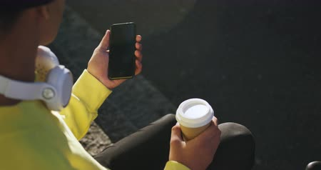 non binary : Rear high angle view of fashionable mixed race transgender adult hanging out on a summer day in the city, sitting in the street, holding cup of coffee and using his smartphone in slow motion. Stock Footage