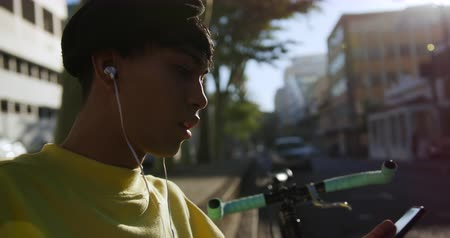 non şehir sahne : Side view close up of fashionable mixed race transgender adult hanging out on a summer day in the city, sitting in the street, putting on his earphones and using his smartphone while his bicycle is leaning against the wall in slow motion.
