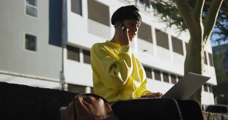 non binary : Side view of fashionable mixed race transgender adult hanging out on a summer day in the city, sitting in the street, sitting on the stairs in the street and using his smartphone and laptop in slow motion.