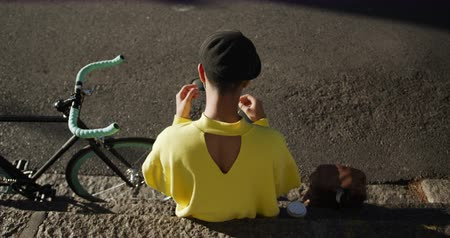 non binary : Rear high angle view of fashionable mixed race transgender adult hanging out on a summer day in the city, sitting in the street, putting on his earphones and using his smartphone while his bicycle is leaning against the wall in slow motion.