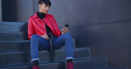 non binary : Front view of fashionable mixed race transgender adult hanging out on a summer day in the city, sitting on the stairs in the street, using his smartphone in slow motion.