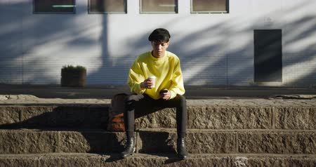 non binary : Front view of fashionable mixed race transgender adult hanging out on a summer day in the city, sitting on the stairs in the street, drinking coffee and using his smartphone in slow motion.