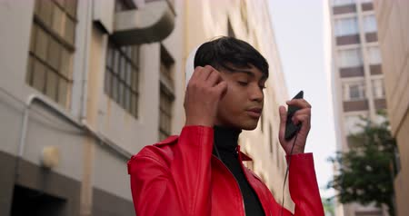 non binary : Side view of fashionable mixed race transgender adult hanging out on a summer day in the city, standing in the street, putting on his headphones in slow motion. Stock Footage