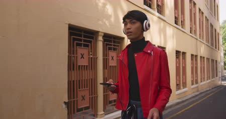 non binary : Front view of fashionable mixed race transgender adult hanging out on a summer day in the city, walking the street, wearing headphones, using his smartphone in slow motion.