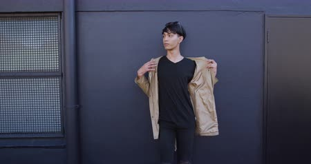 non binary : Side view of a fashionable mixed race transgender adult hanging out on a summer day in the city, standing in the street, putting on his coat in slow motion. Stock Footage