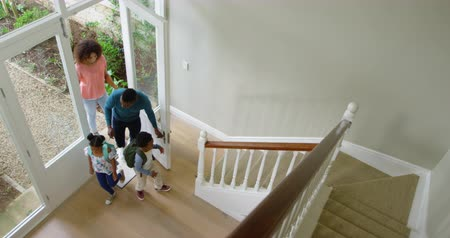 arriving : High angle view of an African American couple with young son and daughter entering the front door in their new home, the children running up the stairs wearing backpacks, slow motion