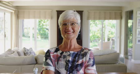 kısa : Portrait close up of a happy senior Caucasian woman with short grey hair and wearing glasses smiling to camera in her living room at home, slow motion