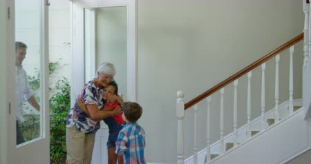domy : Side view of a Caucasian grandfather and grandmother arriving home and being greeted by their young grandson and granddaughter at the front door, the grandmother embracing her granddaughter