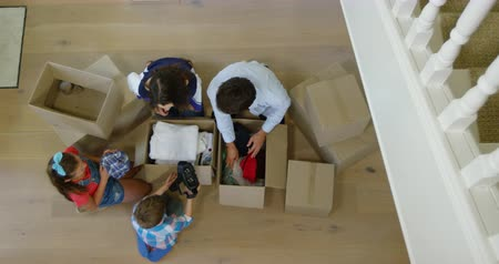 empaque : Overhead view of a Caucasian couple sitting on the floor with their young son and daughter in the hallway of their new home, unpacking cardboard boxes together and smiling, slow motion Archivo de Video