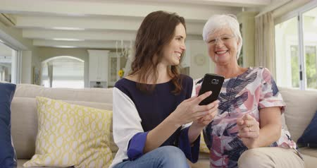 social life : Front view of a senior Caucasian woman and her adult daughter sitting on a sofa in living room using a smartphone together and laughing, slow motion