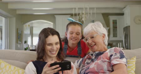 social life : Front view of a senior Caucasian woman with her adult daughter and granddaughter on a sofa in the living room, the daughter using a smartphone to take a selfie of them together, slow motion