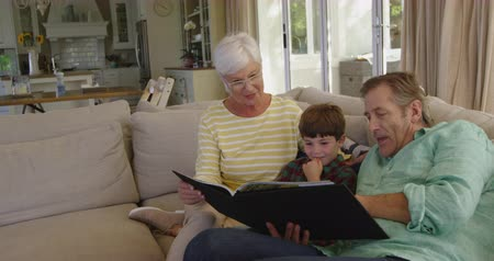 photo album : Front view of Caucasian grandparents sitting on a sofa in the living room looking at a photo album with their young grandson sitting between them, slow motion