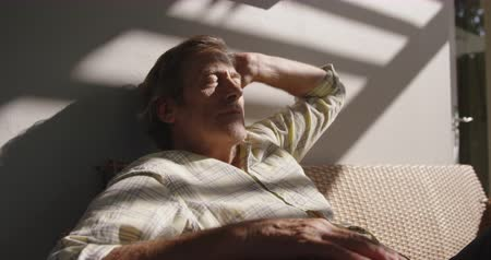 закрытыми глазами : Front view close up of a senior Caucasian man at home sitting on a sofa relaxing with his eyes closed in the sunlight, slow motion Стоковые видеозаписи