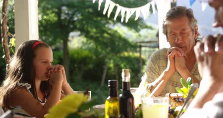 quatro : Front view of a senior Caucasian man sitting outside at a dinner table set for a meal with his adult son, wife and granddaughter, all with eyes closed and hands clasped in prayer before the meal, slow motion