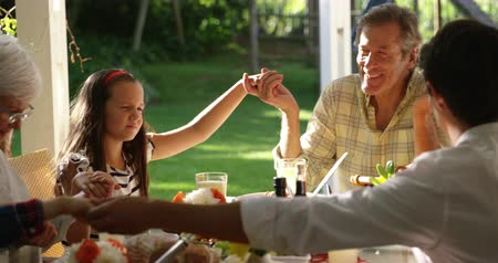 sundurma : Front view close up of a multi-generation Caucasian family sitting outside at a dinner table set for a meal, with eyes closed, holding hands in prayer before their meal, slow motion