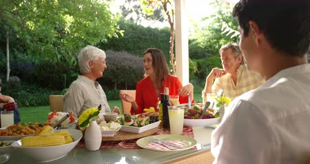 opa en oma : Side view of a Caucasian man sitting outside with his multi-generation family at a dinner table set for a meal, turning and smiling to camera, slow motion