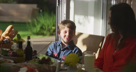 sundurma : Front view of a young Caucasian boy sitting outside in the sun at a dinner table set for a family meal, talking with his mother and smiling, slow motion Stok Video