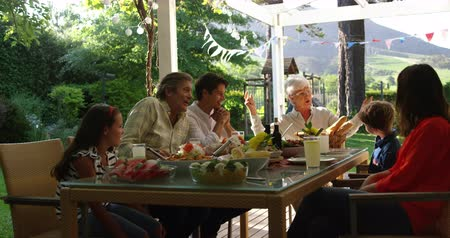 sundurma : Front view of a multi-generation Caucasian family sitting outside at a dinner table set for a meal, talking and laughing, slow motion Stok Video