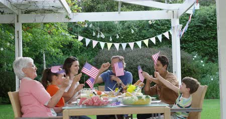 čtvrtý : Front view of a multi-generation Caucasian family sitting outside at a dinner table set for a meal, celebrating and waving US flags, slow motion Dostupné videozáznamy