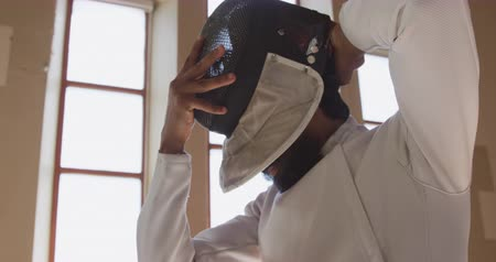 scherma : Low angle side view of a confident focused mixed race male fencer athlete during a fencing training in a gym, wearing jacket and plastron, preparing for a fencing duel, putting mask on in slow motion