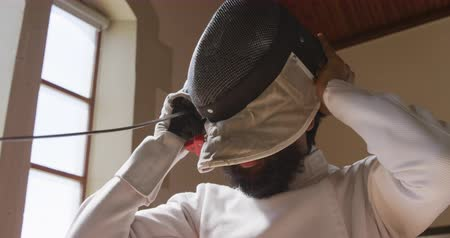 フェンシング : Side view close up of a confident focused mixed race male fencer athlete during a fencing training in a gym, wearing jacket and plastron, preparing for a fencing duel, putting mask on, holding an epee