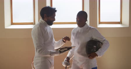 фехтование : Side view of a confident focused mixed race male fencer athlete and mixed race male fencing coach during a fencing training in a gym, discussing training, the man holding a digital tablet in slow motion