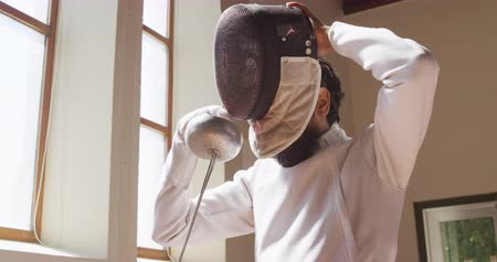 kılıç : Low angle side view of a confident focused mixed race male fencer athlete during a fencing training in a gym, wearing jacket and plastron, preparing for a fencing duel, putting mask on, holding an epee in slow motion Stok Video
