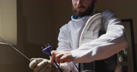 scherma : Low angle front view of a confident focused Caucasian male fencer athlete during a fencing training in a gym, wearing jacket and plastron, preparing for a fencing duel, holding a mask and an epee in slow motion