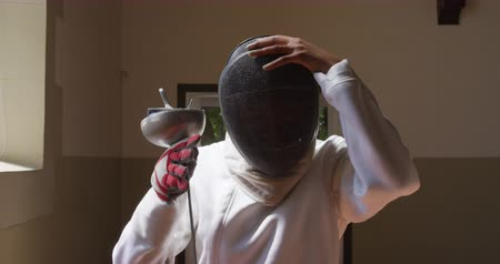 фехтование : Front view of a confident focused mixed race female fencer athlete during a fencing training in a gym, wearing jacket and plastron, preparing for a fencing duel, putting mask on, holding an epee in slow motion