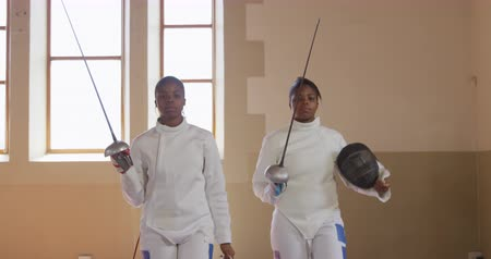 фехтование : Portrait of two focused mixed race female fencer athletes during a fencing training in a gym, walking wearing gloves, jackets, plastrons and holding their epees and masks in slow motion