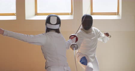 scherma : Front view of a Caucasian and a mixed race female fencer athletes during a fencing training in a gym, sparring in fencing duel wearing masks holding and pointing with epees in slow motion Filmati Stock