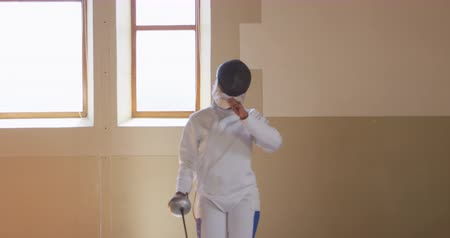 scherma : Portrait of a focused mixed race female fencer athlete during a fencing training in a gym, walking wearing jacket and plastron and pulling her mask back looking at camera holding an epee in slow motion Filmati Stock