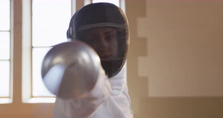 scherma : Front view of a confident focused Caucasian female fencer athlete during a fencing training in a gym, wearing mask, jacket and plastron, preparing for a fencing duel, holding an epee and aiming jumping forward in slow motion