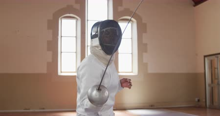 scherma : Front view of a confident focused mixed race female fencer athlete during a fencing training in a gym, wearing mask, jacket and plastron, preparing for a fencing duel, holding an epee and aiming jumping forward in slow motion