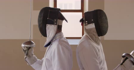 соперничество : Side view close up of a Caucasian and a mixed race male fencer athletes during a fencing training in a gym, sparring in fencing duel wearing masks standing with backs to each other starting their duel in slow motion
