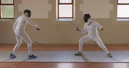 fegyelem : Side view of a Caucasian and a mixed race male fencer athletes during a fencing training in a gym, sparring in fencing duel wearing masks, jumping taking aim at each other with their epees in slow motion Stock mozgókép
