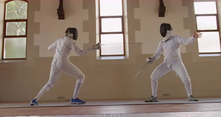 scherma : Side view of a Caucasian and a mixed race male fencer athletes during a fencing training in a gym, sparring in fencing duel wearing masks, jumping taking aim at each other with their epees, one man succeeding in slow motion