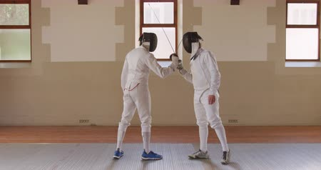 scherma : Side view of a Caucasian and a mixed race male fencer athletes during a fencing training in a gym, sparring in fencing duel wearing masks facing each other crossing their epees in slow motion